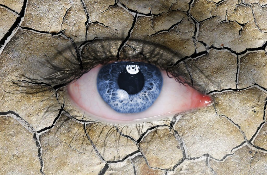 dramatic edit of a close-up shot of a woman's blue eye with the skin stylized into a cracked desert floor