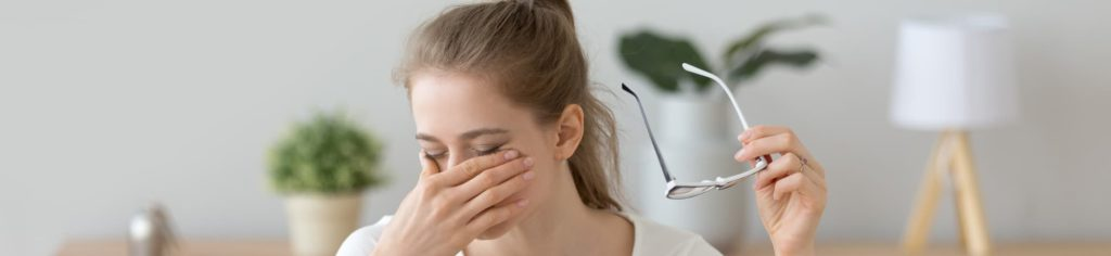 woman rubbing her dry eyes caused by dry air