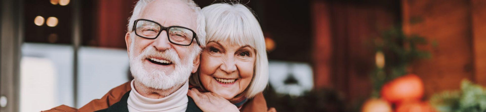 Stylish senior couple smiling after their senior eye exams.