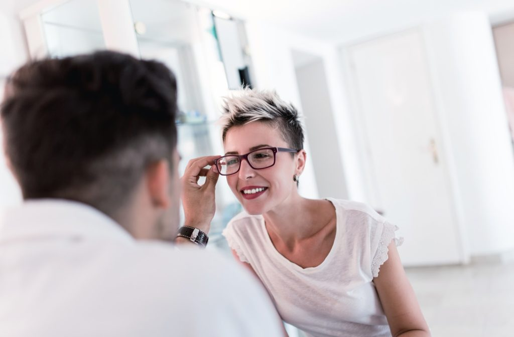 Male optometrist performing eye exam on smiling patient as she looks through eyeglasses