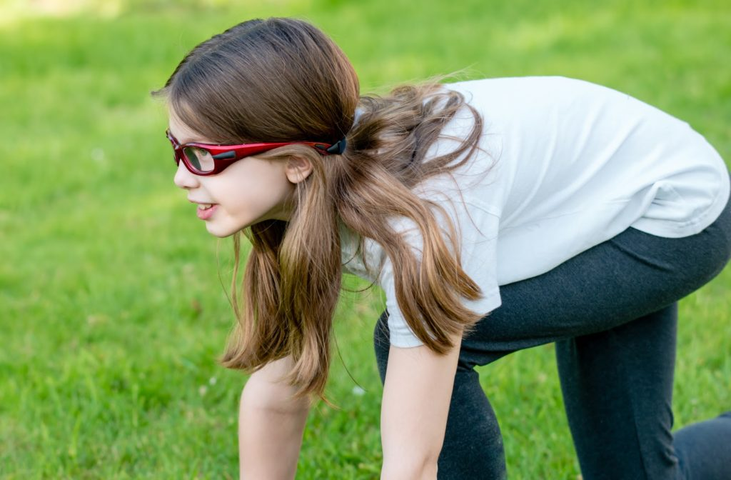 Young girl in running position with safety glasses on.