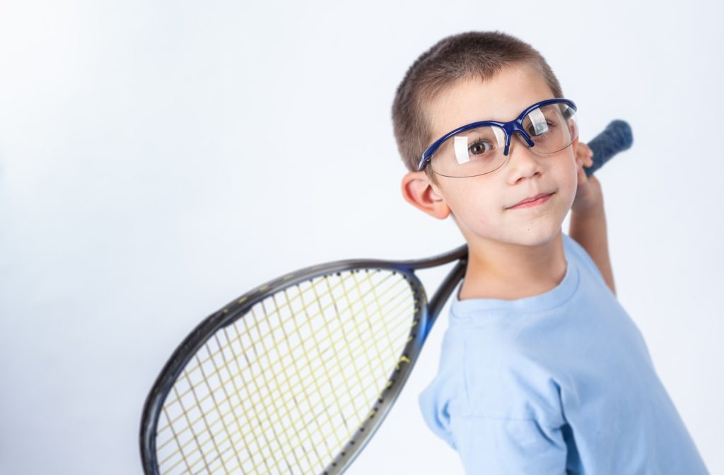 Young boy holding his squad racket and has protective eyewear on.