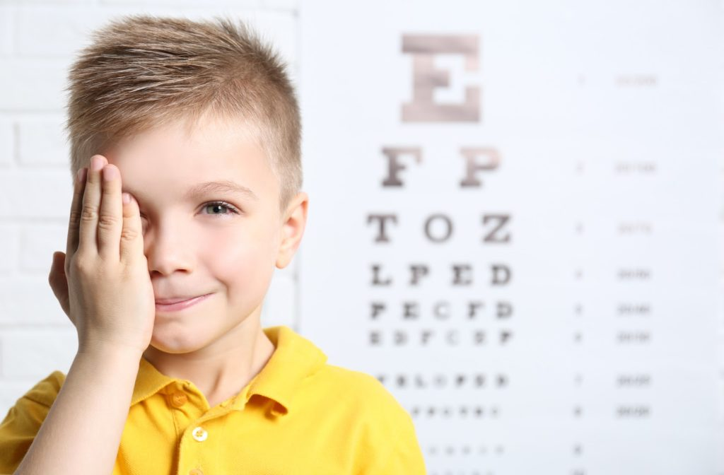 Young boy covering up right eye with eye exam chart in the background